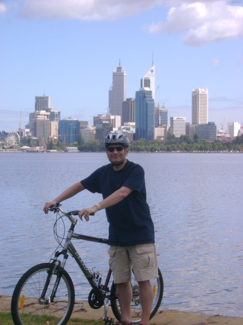 Imran on bike, city in background