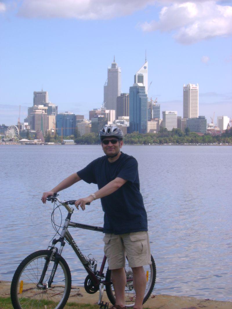 Imran on bike, city in background